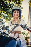 Casual smiling blond woman in moto helmet. Posing on scooter on nature background Stock Images