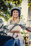 Casual smiling blond woman in moto helmet. Posing on scooter on nature background Stock Photos