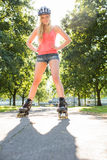 Casual smiling blonde standing hands on hips wearing inline skates Stock Image