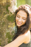 Casual smiling brunette embracing a tree with closed eyes Royalty Free Stock Image