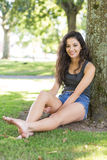 Casual smiling brunette sitting leaning against tree Stock Images