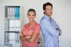 Casual smiling business team standing back to back. In the office Stock Images
