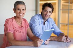 Casual smiling business team working at desk using tablet Royalty Free Stock Images