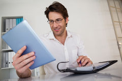 Casual smiling businessman organizing his schedule at his desk Royalty Free Stock Image