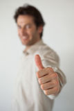 Casual smiling businessman showing thumbs up to camera Stock Image
