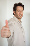 Casual smiling businessman showing thumbs up to camera Stock Photos