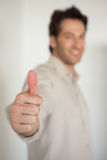 Casual smiling businessman showing thumbs up to camera Royalty Free Stock Photo