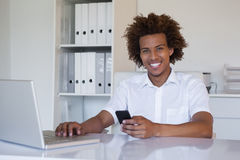 Casual smiling businessman using his smartphone and laptop at his desk Royalty Free Stock Photos