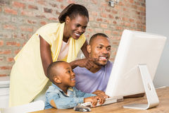 Casual smiling family on a computer Royalty Free Stock Photos