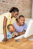 Casual smiling family on a computer Royalty Free Stock Images