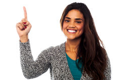Casual smiling girl pointing upwards Royalty Free Stock Image