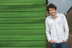 Casual Smiling Guy Leaning Against Green Wall Stock Images