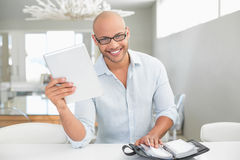 Casual smiling man with digital tablet and diary at home Royalty Free Stock Photography