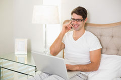Casual smiling man using cellphone and laptop in bed Royalty Free Stock Photography