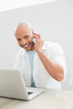 Casual smiling man using cellphone and laptop at desk Stock Image