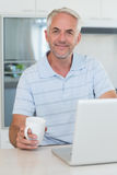 Casual smiling man using his laptop while having coffee Stock Photography