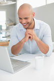 Casual smiling man using laptop at home Stock Images
