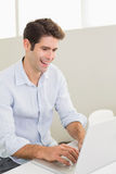 Casual smiling man using laptop at home Royalty Free Stock Images