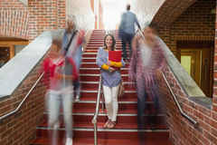 Casual smiling student standing on stairs Stock Photo