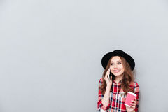 Casual smiling woman in hat talking on mobile phone Stock Photography