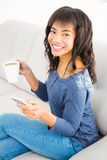 Casual smiling woman holding coffee and smartphone. At home Royalty Free Stock Image