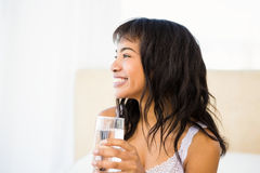 Casual smiling woman holding a glass of water Stock Photos