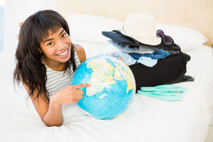 Casual smiling woman touching globe on the bed Stock Photo