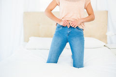 Casual smiling woman trying to close her jeans Stock Images