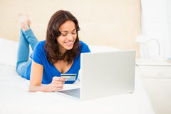 Casual smiling woman using laptop while holding a card Royalty Free Stock Image