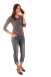 Casual smiling woman using smartphone on white background. Stock Photo