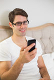 Casual smiling young man text messaging in bed Stock Photography