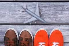 Casual sport shoes and toy plane. Wooden desk surface background Stock Photos