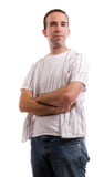 Casual Stance. A young man dressed in casual clothing is standing with his arms crossed, isolated against a white background Royalty Free Stock Photo