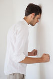 Casual stresed businessman leaning against the wall Royalty Free Stock Image