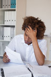 Casual stressed businessman going over paperwork at his desk Stock Images