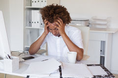 Casual stressed businessman with his head down at desk Royalty Free Stock Images