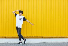 Casual student dancing to the music on a yellow wall background. Active lifestyle concept. Copy space. Active, beautiful modern asian young student enjoying Royalty Free Stock Image