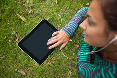 Casual student lying on grass using tablet listening to music Royalty Free Stock Images