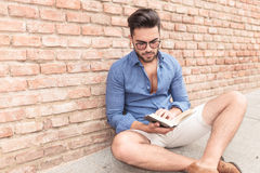 Casual student reading a book while seated. Near brick wall Royalty Free Stock Photos