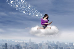 Casual student using tablet on the cloud Stock Photo