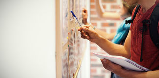 Casual students searching something on notice board Royalty Free Stock Photos