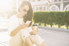 Beautiful girl using phone while sitting with cup of coffee. Casual style girl using phone while sitting with paper cup of coffee in summer morning in city royalty free stock photography