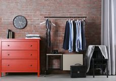 Casual stylish male clothes on hanger stand. In room Stock Photos