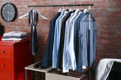 Casual stylish male clothes on hanger stand. In room Royalty Free Stock Image