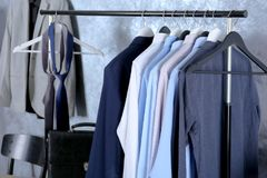 Casual stylish male clothes on hanger stand. In room Royalty Free Stock Photos