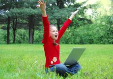 Casual success girl on a laptop in a green grass Royalty Free Stock Image