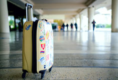 Casual suitcase with many colorful stickers standing at airport Stock Photography