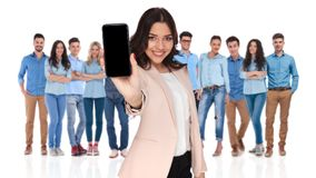 Casual team with businesswoman leader showing telephone screen i. Young casual team with smiling businesswoman leader showing blank telephone screen in front royalty free stock photo