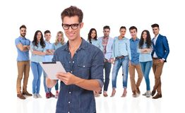 Casual team with young leader working on tablet in front. Casual team with young leader wearing glasses working on tablet in front while standing on white royalty free stock photo