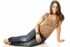 Casual teen. Pretty brunette sitting in casual jeans and t-shirt with jewelry accents Royalty Free Stock Photos